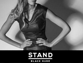 Nærbilde av dame iført sort kjole fra Stand Black Nude. Inneholder logo. Bildet blir brukt som knapp til kategorien Stand Black Nude i nettbutikken